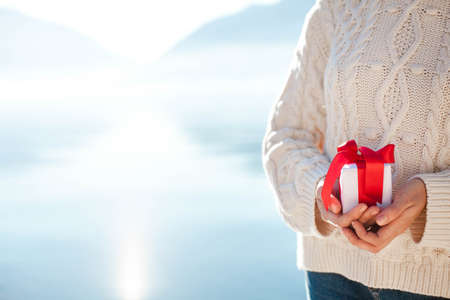 Young woman holding gift box with red ribbon. Female hands with present. Blue background of winter sea beach and mountains. Girl in white knitted sweater outdoor. Happy Christmas. Copy space. Close up