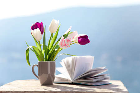 Tulips and opened book at wooden table outdoors. Spring still life at sea beach. Blooming flowers on balcony at blue background of mountains. Pink, white, purple bouquet. Copy space.