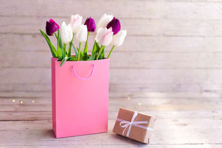 Tulips and gift box at wooden background. Presents for spring holidays. Blooming flowers in pink shopping bag. White, lilac and purple bouquet. Still life in morning sun light. Copy space.