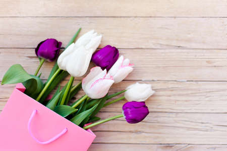 Tulips at wooden background. Presents for spring holidays. Blooming flowers in pink shopping bag. White, lilac and purple bouquet. Flat layout. Copy space.