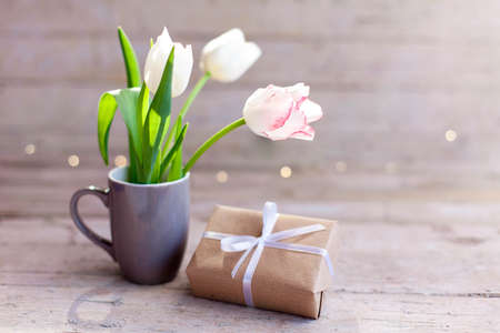 Tulips and gift box at wooden background. Present for spring holidays. Blooming flowers in gray cup. Bouquet in vase. Pink, white flora in morning sun light. Cozy still life. Copy space.