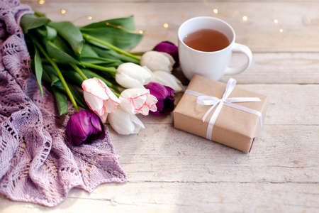 Tulips, gift box and cup of tea at wooden background. Blooming flowers and present for holidays. White, pink, lilac and purple bouquet. Morning surprise. Spring still life. 写真素材