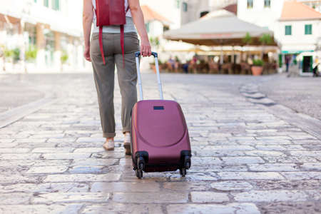 Girl traveler with suitcase is mooving on paving stone to old town. Woman tourist is searching direction. Concept of travel, vacation, solo female tourism, trip, journey.