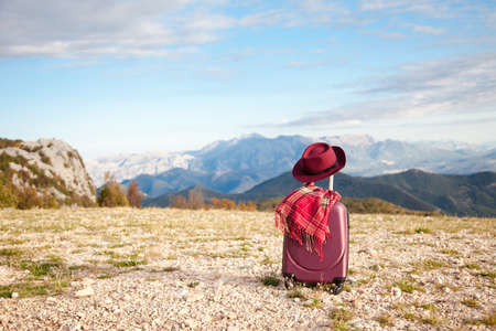Suitcase with felt burgundy hat and cozy plaid scarf in autumn mountains. Concept of travel, vacation, female tourism, trip, adventure. Nature background of amazing landscape with blue sky.
