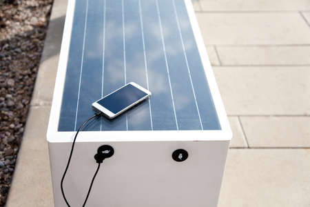 Solar panel on bench. Mobile phone charging via USB from solar power outdoors. Alternative electricity source. Concept of sustainable resources, free, renewable energy, ecology, modern technology.