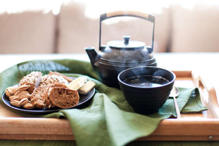 Still life of black teapot, mug of steamy green tea in cozy home interior. Cup of hot beverage, food, plate of rye bread, almond are on wooden serving tray. Breakfast on table in morning warm sunlight