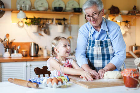 Grandmother and granddaughter are cooking in cozy home kitchen. Family is happy together. Senior woman and cute little child girl are smiling. Kid is helping to make bakery and homemade cakes.