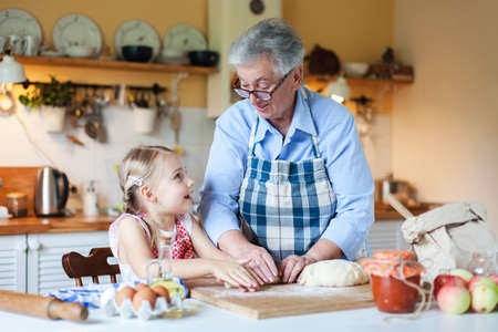 Grandmother and granddaughter are cooking in cozy home kitchen. Family is happy together. Senior woman and little child girl are smiling. Cute kid is helping to prepare for Thanksgiving Day dinner. Banco de Imagens