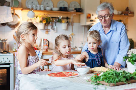 Family and kids cooking pizza in cozy home kitchen. Grandmother and three sisters preparing homemade italian food. Funny little girls helping senior woman, eating ingredients. Children chef concept
