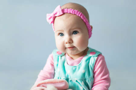 Pretty baby girl with sweet cute pink cheeks. Child has blue eyes, headband with bow. Little baby is wearing in children dress and clothes. Blue light background.