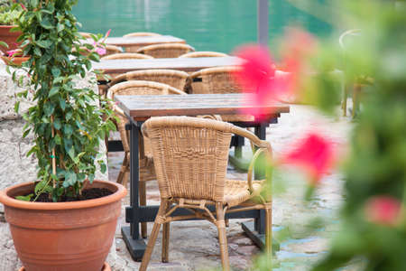 Authentic cafe with wooden rustic tables and wicker chairs. Amazing country landscape with green mountains, sea, green plants, red, pink flowers. Boka Kotor Bay view from Perast in Montenegro.