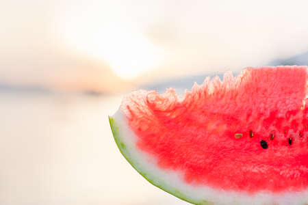 Slice of red watermelon on sea beach at sunset outdoors. Summer fun holiday and travel, vacation concept.