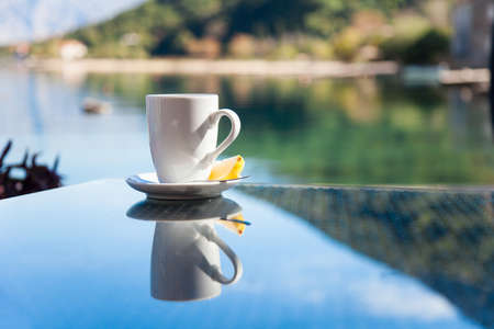 Cup of tea with lemon is on glass table. Beach cafe outdoors in resort. Concept of holiday, relaxation, traveling.