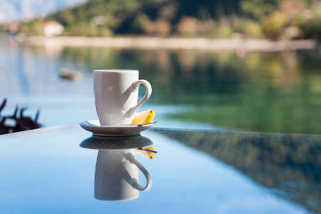 Cup of tea with lemon is on glass table. Beach cafe outdoors in sea resort with view of mountains. Concept of holiday, relaxation, traveling. Banco de Imagens