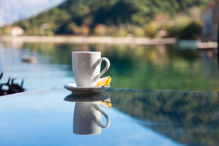 Cup of tea with lemon is on glass table. Beach cafe in sea resort with view of mountains outdoors. Concept of holiday, relaxation, traveling.