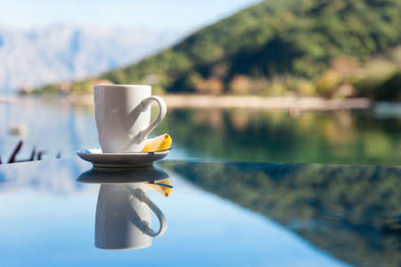 Cup of tea with lemon is on glass table. Beach cafe outdoors in sea resort with view of mountains. Concept of holiday, relaxation.