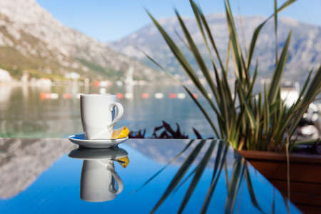 Cup of tea with lemon is on glass table. Beach cafe outdoors in sea resort by mountains. Concept of holiday, relaxation, traveling.