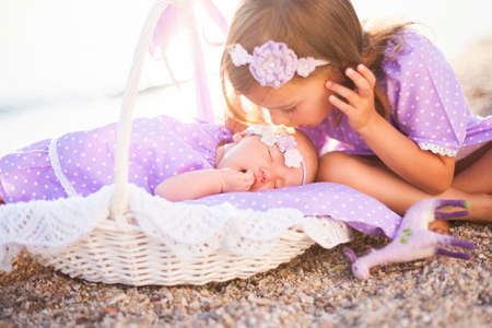 Little sisters are on sea beach. Two girls are in lilac and lavender dresses. Baby is sleeping in wicker basket or cradle. Kid is kissing small child. Concept of childhood, tenderness, love. Banco de Imagens