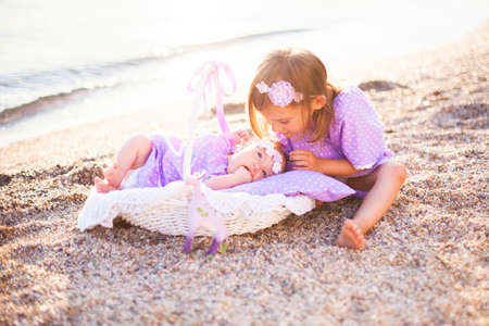 Little sisters are on sea beach. Two girls are in lilac and lavender dresses. Baby lies in wicker basket or cradle. Kid is playing with infant. Concept of childhood, tenderness, love. Banco de Imagens
