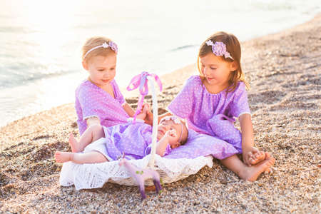 Little sisters are on sea beach. Three girls are in lilac and lavender dresses. Kids play with infant. Baby lies in wicker basket or cradle. Concept of childhood, tenderness, family, love. Banco de Imagens
