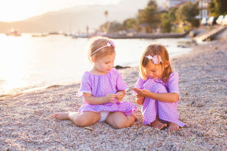 Little sisters are on sea beach. Two girls are in lilac and lavender dresses. Kids play with sand and pebbles. Concept of childhood, tenderness, family, friendship, love.