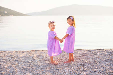 Little girls are on sea beach. Two sisters are in lilac and lavender dresses. Kids hold hands and play. Concept of childhood, tenderness, family, friendship. Banco de Imagens