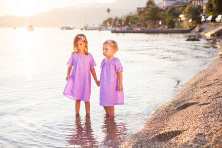 Little girls are on sea beach. Two sisters are in lilac and lavender dresses. Kids hold hands and play in water. Concept of childhood, tenderness, family, friendship. Banco de Imagens
