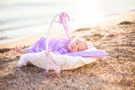 Little girl on sea beach. Baby is wearing in lilac and lavender dress. Infant lies in wicker basket or cradle with pillow. Concept of childhood, tenderness.