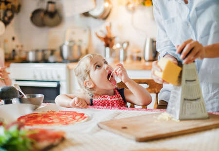 Family cooking pizza in kitchen. Mother and daughter preparing homemade italian food. Funny little girl is helping woman, eating and tasting cheese and ingredients. Children chef concept.