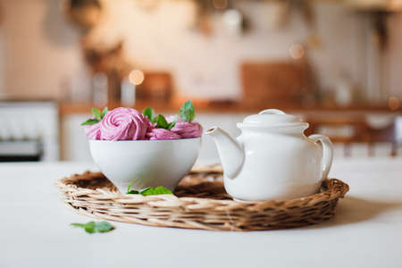 White teapot and pink dessert are serving on straw wicker tray on table. Tea time, cozy atmosphere. Kitchen still life on background with warm light. Sweets are decarated with herbal mint leaves. Banco de Imagens