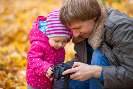 Little kid is playing with camera in autumn park. Daughter and father look at taking photos of autumn nature, landscapes. Baby girl is dressed in warm hat and jacket.