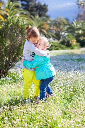 Two little girls are hugging. Sisters are on spring chamomile flowers meadow near palms and mountains. Kids are wearing in blue and yellow jeans. Concept of childhood, friendship, love, family.