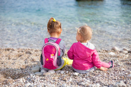 Two little kids are sitting by sea. Sisters are on pebble beach. Girls are wearing in bright, pink clothes. Concept of friendship, childhood, love, family. Banco de Imagens