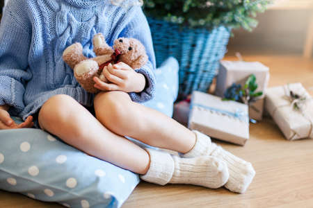Little child girl near Christmas tree. Kid in woolen knitted socks and sweater is sitting with toy bear on pillow on warm floor at home. Presents, gifts are under fir tree in basket. Blue decorating.