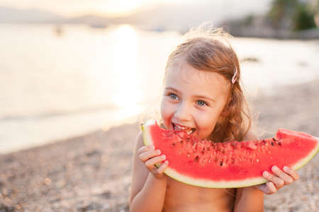 Girl is holding slice of red watermelon on beach at sunset. Summer fun holiday and travel concept. Child is happy tourist in sea resort during vacation outdoors. Kid is smiling, enjoying eating fruit. Banco de Imagens
