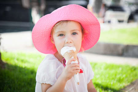Little girl is enjoying and holding melting ice cream in cones in her hands. Child is eating gelato in resort outdoors in town streets. Concept of childhood, summer, traveling.