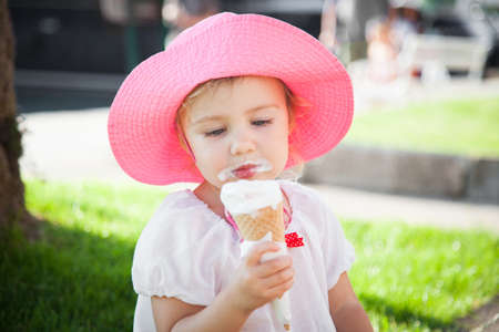 Little girl is enjoying and holding melting ice cream in cones in her hands. Child is eating gelato in resort outdoors in town streets