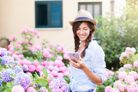 Happy girl is using smartphone. Woman with smile in country garden and bushes of hydrangea. Pink, blue flowers are blooming in town street by house. Lifestyle of gardener and florist, business.