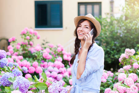Happy girl is talking and using smartphone. Woman with smile in country garden and bushes of hydrangea. Pink, blue flowers are blooming in town street by house. Lifestyle of gardener and florist.