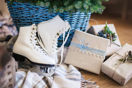 Gifts, presents and white children skates are under natural Christmas tree in basket on wooden warm floor and beige cozy plaid. Blue decorating in rustic style with kraft paper, natural materials.