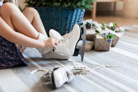 Little child girl tries on children skates near Christmas tree. Kid is getting gifts, presents and going skate. Blue decorating in rustic style with natural materials. Banco de Imagens