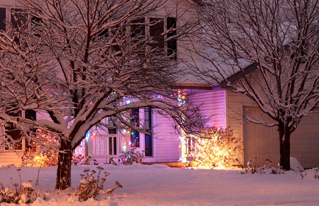 House entrance decorated with glowing lights for winter holidays and lots of snow. Night scene. Christmas and New Year holiday background.