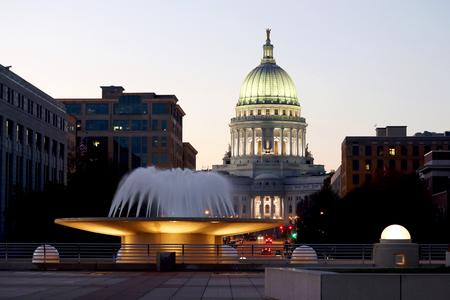 De het Capitoolbouw van de Staat van Wisconsin, Nationaal Historisch Oriëntatiepunt. Madison, Wisconsin, VS. Na zonsondergangscène met officiële gebouwen en verlichte fontein op de voorgrond. Uitzicht vanaf Monona terras balkon, horizontale samenstelling.
