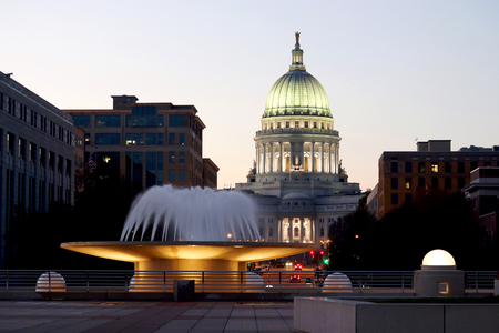 Wisconsin State Capitol building, National Historic Landmark. Madison, Wisconsin, USA. After sunset  scene with official buildings and illuminated fountain on the foreground. View from Monona terrace balcony, horizontalcomposition.