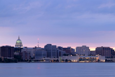 Downtown skyline of Madison, the capital city of Wisconsin, USA.After sunset view with State Capitol building dome against beautiful bright sky as seen across lake Monona.