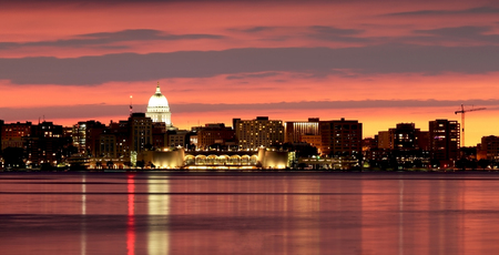 Downtown skyline of Madison, the capital city of Wisconsin, USA. After sunset view with State Capitol building dome and Monona Terrace against beautiful bright sky and reflection in lake water as seen across lake Monona.