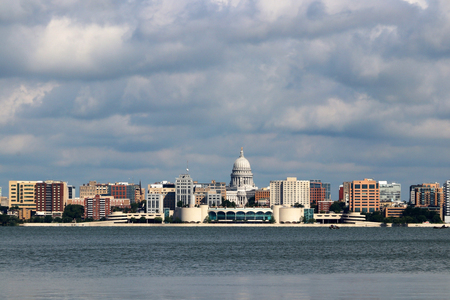Downtown skyline of Madison, the capital city of Wisconsin, USA. Morning view with State Capitol and official buildings in sunlight against beautiful cloudy sky and lake water as seen across lake Monona. 版權商用圖片