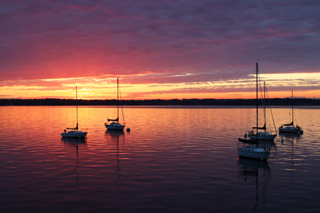 Amazing summer evening landscape with group of drifting yachts on a lake during spectacular sunset. Bright sky reflects in the lake water.
