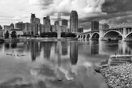 Minneapolis downtown skyline and Third Avenue Bridge above Mississippi river in black and white. Midwest USA, Minnesota state.