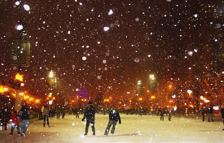 시카고에서 눈 덮인 밤 동안 아이스 스케이팅을 즐기는 사람들.